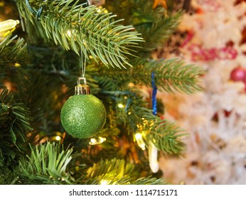 A sparkling green glittered Christmas tree ornament hanging from a branch in an artificial green Christmas tree with a white Christmas tree in the background.
