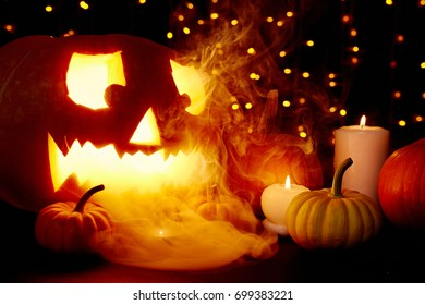 Sparkling Halloween background with burning candles and smoke over pumpkins