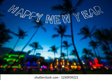 Sparkling Happy New Year message hanging in silver bunting over brightly colored tropical background of the Miami skyline in defocus