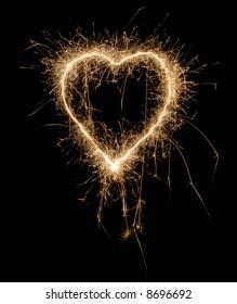 Sparkling heart made of fireworks on black background