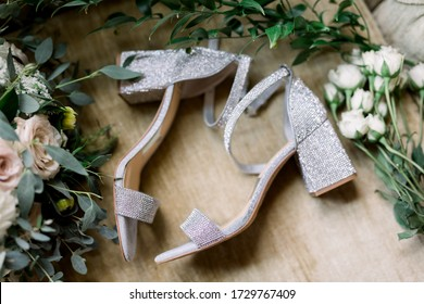 Sparkling High Heels Lying on Their Sides in the Middle Between Loose Flowers