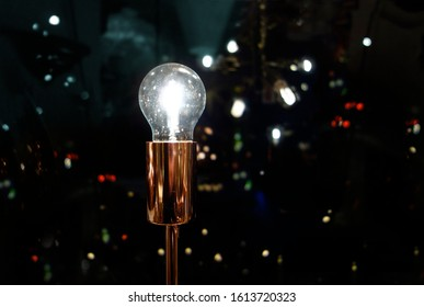 Sparkling Light bulb with night time modern urban background, symbolizing bright ideas in modern urban life