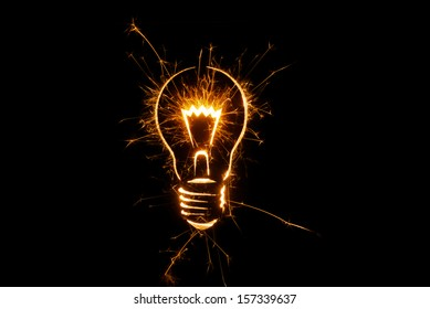 Sparkling light bulb on black background with ample copy space.
