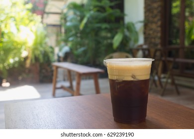 Sparkling Nitro Cold Brew Coffee on wooden table outdoor cafe ready to drink