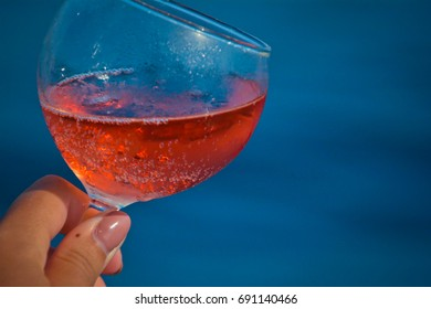 Sparkling pink wine in a glass (champagne).