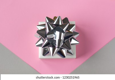 Sparkling present box with silver bow on pink background. Flat lay style. Place for text.