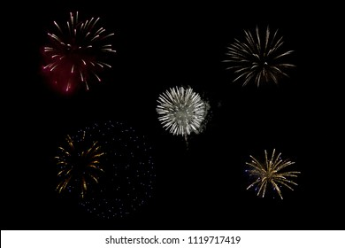 Sparkling round fireball charges exploding in pitch black sky on 4th of July celebration night