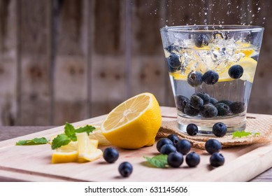 Sparkling water blueberries with lemons on wood background.