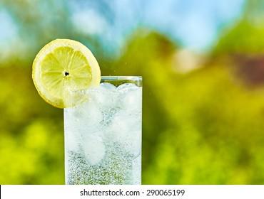 Sparkling Wasser und Zitronenscheibe auf Glas mit Eis, sonniger Tag - enger Fokus auf die Mitte des Glases