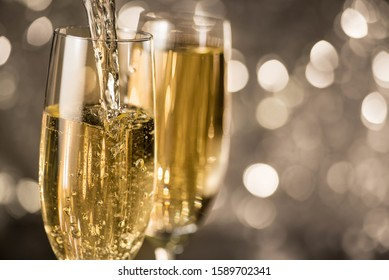 Sparkling white champagne is poured into a glass on a golden bokeh circles background. Christmas and New Year holidays celebration.