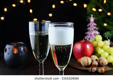 Sparkling white wine in two glasses on Christmas table. Christmas tree, lights and decorations in the background.