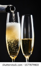 sparkling wine pouring from bottle into glasses for celebrating christmas, isolated on black