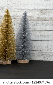 Sparkly gold and silver bottle brush Christmas trees against a wooden background, portrait orientation