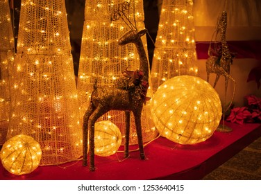 Sparkly reindeer figures in front of festive Christmas display