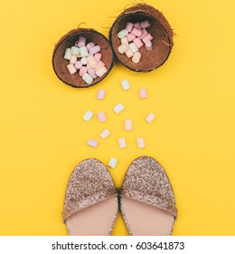 sparkly sandals with golden color and tropical coconut with a marshmallow on a yellow background. beauty and fashion.