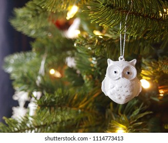 A sparkly white ceramic owl Christmas tree ornament with glitter hangs from a branch of a Christmas tree with glowing golden lights.