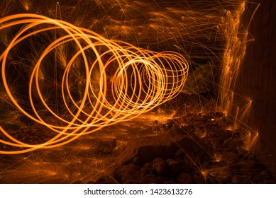 Sparks created by Bernd steel wool in a long exposure shote, Sparks created yellow orang faire spiral in a dark cave, Steel wool photography,  Iron wool, Wire wool, Steel wire, Wire sponge