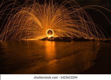 Sparks created by Bernd steel wool in a long exposure shote, Sparks created yellow orang faire spiral in a beach at night, Steel wool photography,  Iron wool, Wire wool, Steel wire, Wire sponge