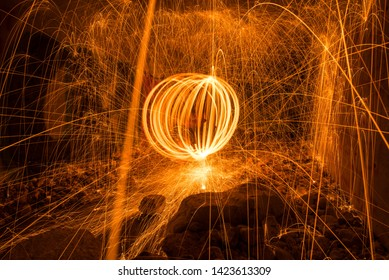 Sparks created by Bernd steel wool in a long exposure shote, Sparks created yellow orang faire boll in a dark cave, Steel wool photography,  Iron wool, Wire wool, Steel wire, Wire sponge