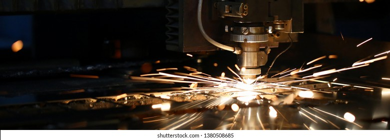Sparks fly out machine head for metal processing laser metal on metallurgical plant background. Manufacturing finished parts for automotive production concept
