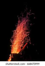 Sparks fly from a roaring fire in a chiminea at night.
