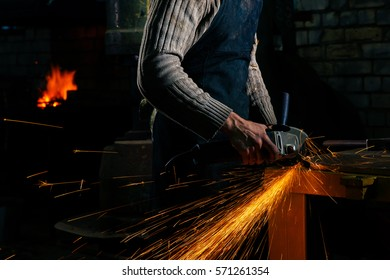Sparks flying over the working table during metal grinding.