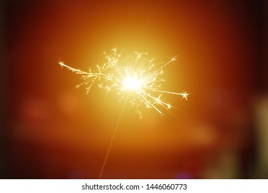 Sparks from hand cold fireworks bright sun orange brown background