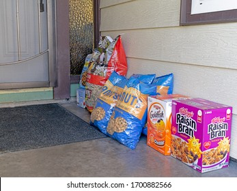 Sparks, Nevada / USA - April 11, 2020: Boxes and bags of groceries stacked on a residential porch. Delivered by a delivery service from e-commerce online shopping. Safe shopping concept.