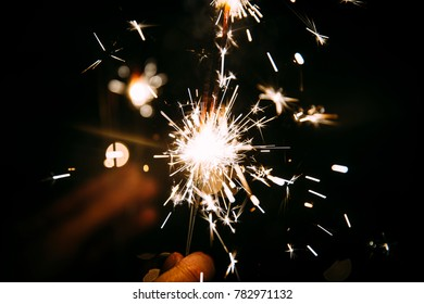 Sparks from a new year pyrotechnic sparkler with bokeh in the background