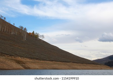 A sparse mountainside next to a lake in Utah against a blue sky with clouds