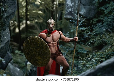 Spartan soldier with stunning sexy muscular torso standing in the woods posing with his shield and spear.