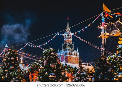Spasskaya tower of Kremlin among New Year festive decorations on Red Square, main landmark in Moscow. Christmas fair in Russia at evening while snow falling