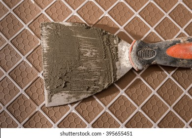 Spatula for laying tiles on the reverse side of separate tile.