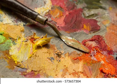 spatula on a palette with oil paints. yellow paint, extruded from the tube