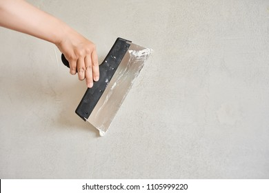 Spatula with putty in hand. Worker puts of plaster on wall.