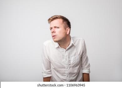 Speak loudly. Caucasian man having hearing problem listening to something