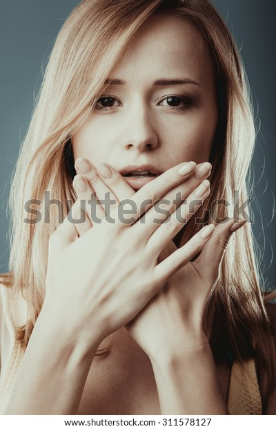 Speak no evil concept. Surprised woman face covering her mouth with hands close up