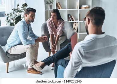 Speak out. Young married couple talking while sitting on the therapy session with psychologist