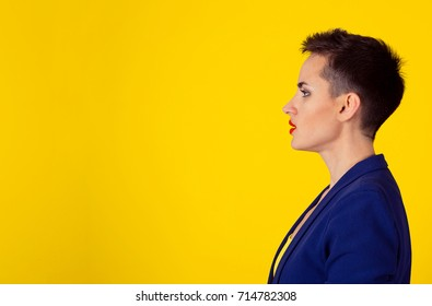Speak, sound concept. Side profile portrait of a pretty serious woman speaking. Girl short hair red lips blue suit yellow shirt isolated yellow background wall with copy space