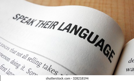 Speak their language word on a book. Business success concept