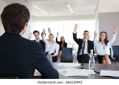 Speaker at business conference and audience asking questions