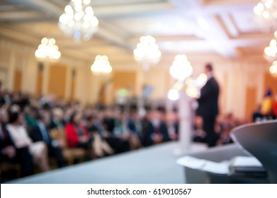 Speaker at business conference. Business executive delivering presentation to colleagues during meeting or in-house business training, explaining business plans to employees. blurred. Audience at hall