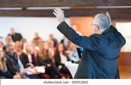 Speaker at Business Conference with Public Presentations. Audience at the conference hall. Rear view. Horisontal composition. Background blur.