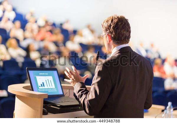 Conferenciante en la Conferencia Empresarial con Presentaciones Públicas. Audiencia en la sala de conferencias. Club de emprendedores. Vista trasera. Composición histórica. Borroso fondo.