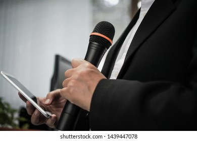 Speaker or businessman hold Microphone for speech or speaking in seminar Conference room, talking for lecture to audience university, Computer monitor desk Background. Business Presentation concept