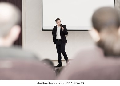 speaker conducts the business of the conference standing in front of a large white screen on the stage in the conference room
