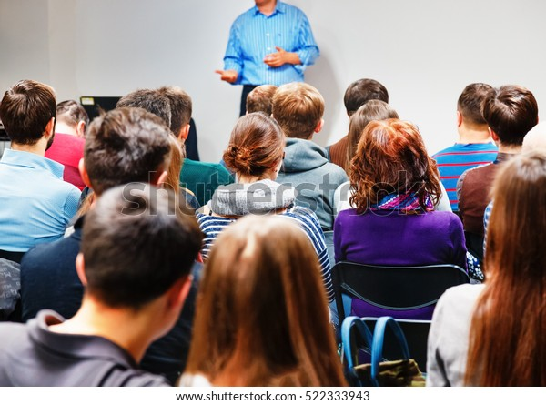 Speaker explain essence method with hand-play gesticulation, group of people students are listening attentively, romantic couple of students at foreground.
