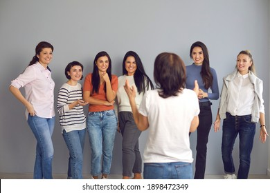 Speaker giving motivational talk to female audience. Group of happy smiling women in their 20s and 30s standing and listening to an interesting presentation by professional lifestyle or business coach