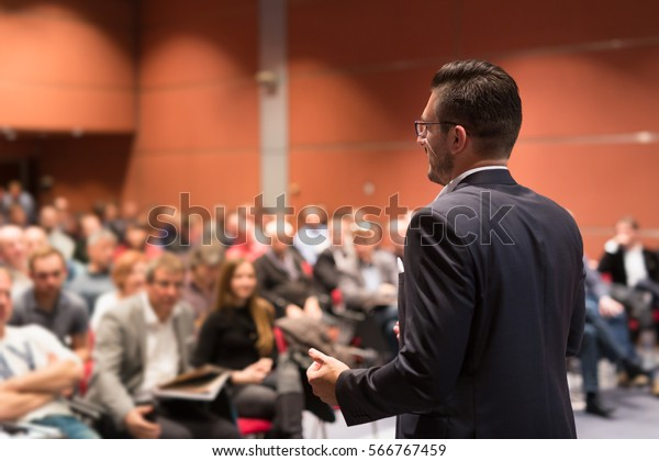 Speaker giving talk at business conference event. Audience at conference hall. Business and Entrepreneurship concept.
