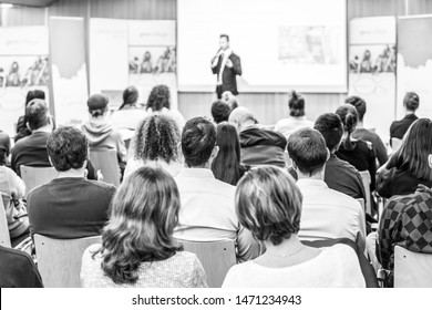 Speaker giving talk at business event. Audience at the conference hall. Business and Entrepreneurship concept. Focus on unrecognizable people in audience. Black and white.